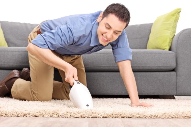 Young joyful man vacuuming a carpet with a handheld vacuum cleaner