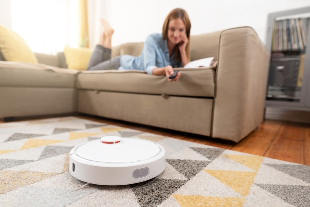 Robotic vacuum cleaner cleaning the room while woman relaxing on sofa