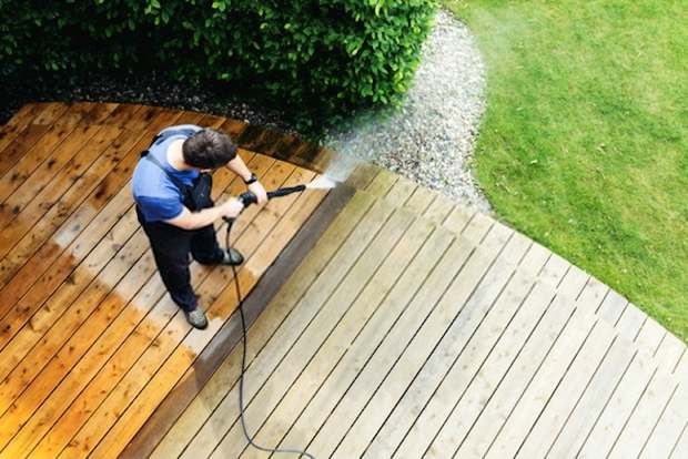 A detailed picture showing someone cleaning his compound using a pressure washer