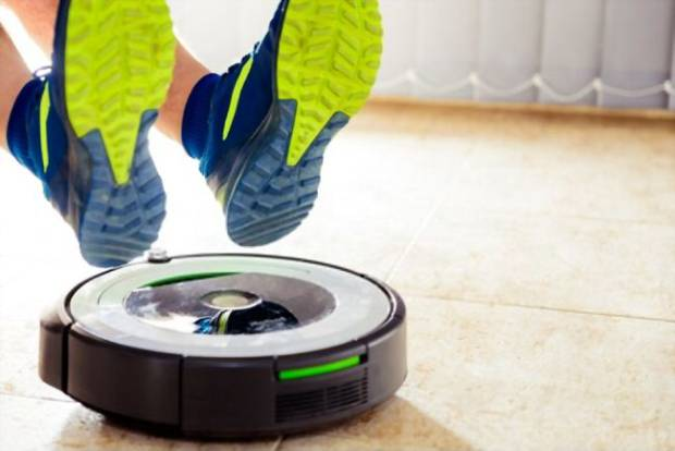 A picture showing someone's shoes near a Roomba gadget
