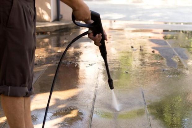 A close up picture showing someone cleaning his home using a pressure washer