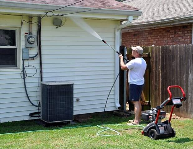 A picture showing a man using a pressure washer