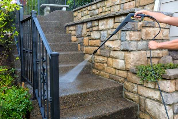 A close up picture showing someone cleaning his stairs using a pressure washer