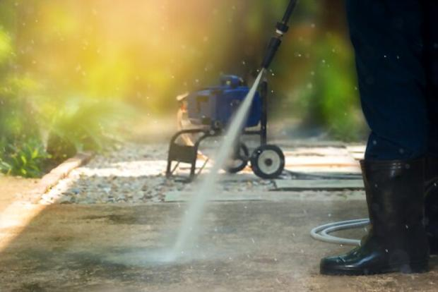 A close up picture of someone cleaning his pathway using a pressure washer