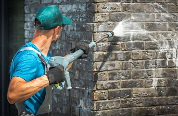 A cleaner wearing gloves while using a pressure washer