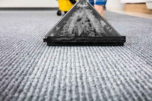 Someone cleaning their carpet using a vacuum cleaner