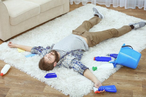 A young man tired and sleeping on a dirty carpet